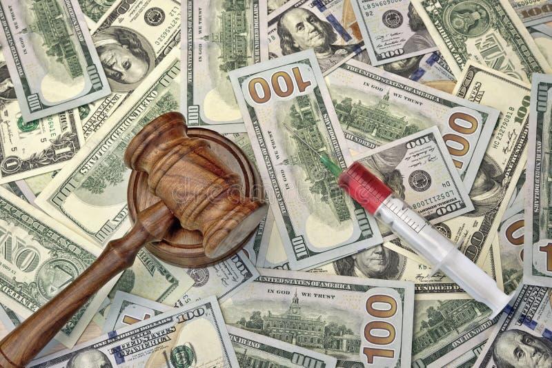 Juizes martelo e seringa com injeção no dinheiro Backgroun do dólar imagens de stock royalty free
