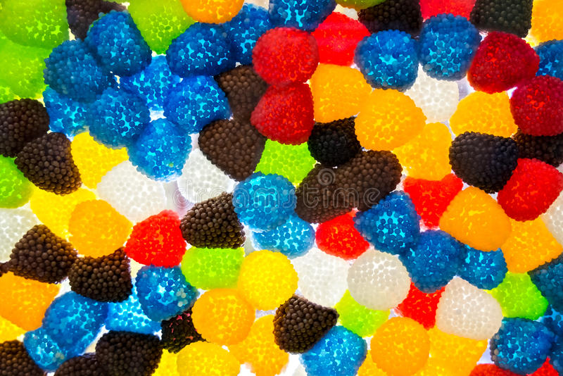 Jujube in de vorm van de suikerafwezigheid van bessen, aardbeien en moerbeibomen, kleurrijke abstracte textuurachtergrond, achter royalty-vrije stock afbeeldingen