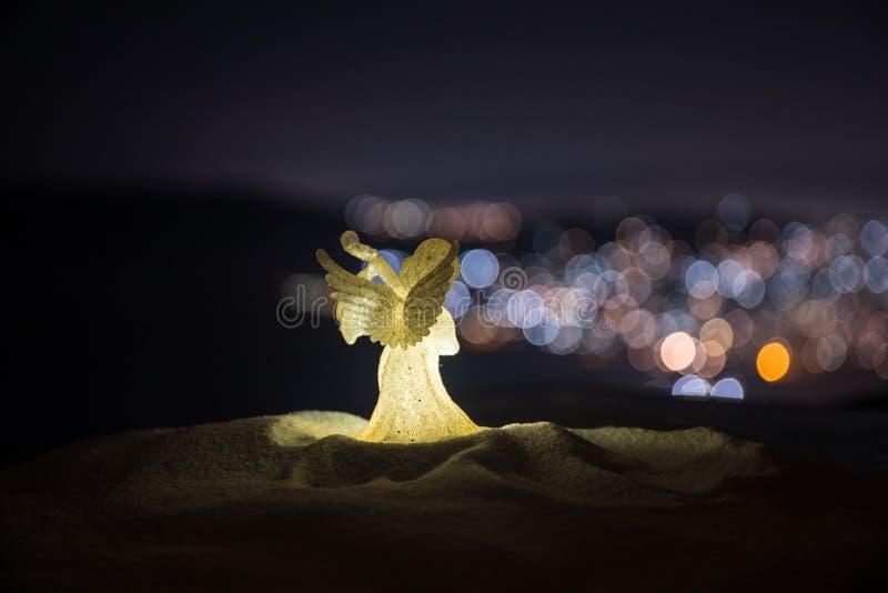 julängel på ljus för suddighetsbokehstad på natten på bakgrund Liten vit skyddsängel i snö arkivbilder