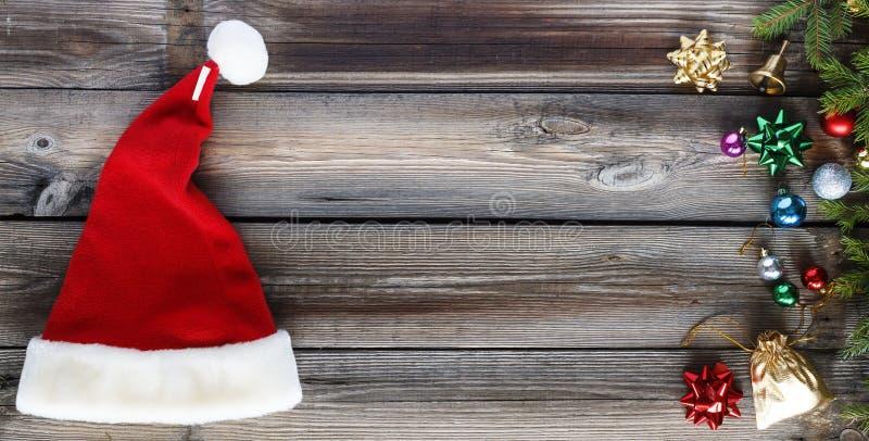 Jul bakgrund, Santa Claus hatt, julpynt, träbakgrund Lekmanna- lägenhet, kopieringsutrymme Top beskådar royaltyfri fotografi