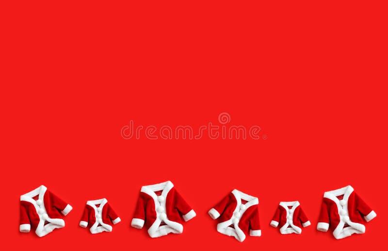 Jul bakgrundsSanta Claus Saint Nicholas mini- röda som lag passar dräkter lägger framlänges, isolerad färgglad stor tom bakgrund royaltyfria foton
