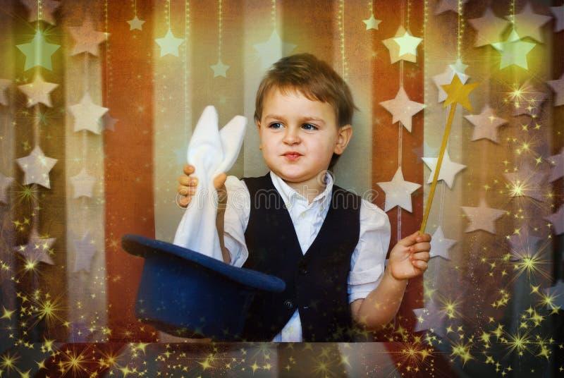 Jul behandla som ett barn trollkarlhandtag en kanin ut ur öron för en hatt royaltyfria foton