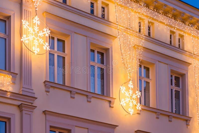 Jul dekorerad husfasad med den skinande snöflingan arkivfoton