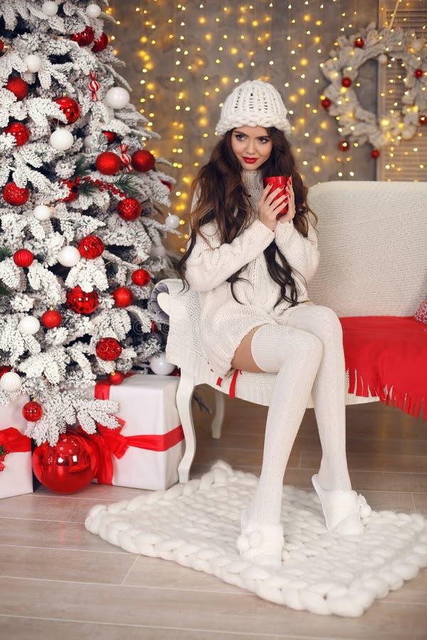 Jul Den härliga nätta kvinnan i den vita stickade plaggtröjan, den handgjorda hatten och hemtrevliga sockor kopplar av på den sta fotografering för bildbyråer