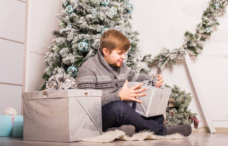 Jul - den lyckliga le caucasian mannen öppnar gåvaasken arkivbild