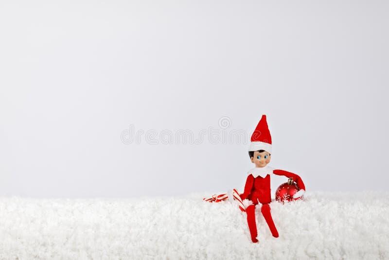 Jul Elf sitter på en Snowy Shelf med Peppermint Sticks och Ornament royaltyfria foton