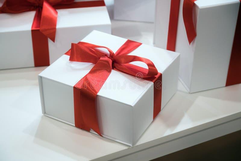 Jul eller födelsedagtid Gåvaaskar med röda band på träskrivbordbakgrund royaltyfri foto