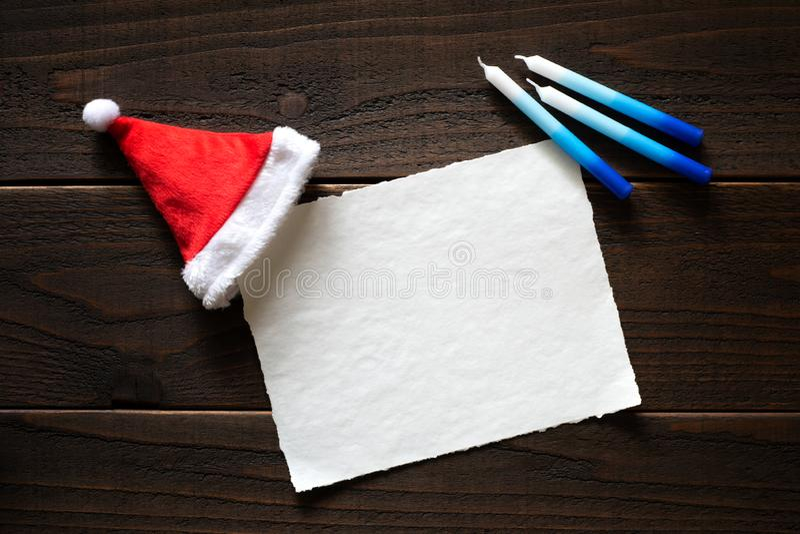 Jul eller kort för Chrismukkah feriepapper med röda och vita Santa Claus Hat och Chanukkahstearinljus på den mörka lantliga träta royaltyfri bild