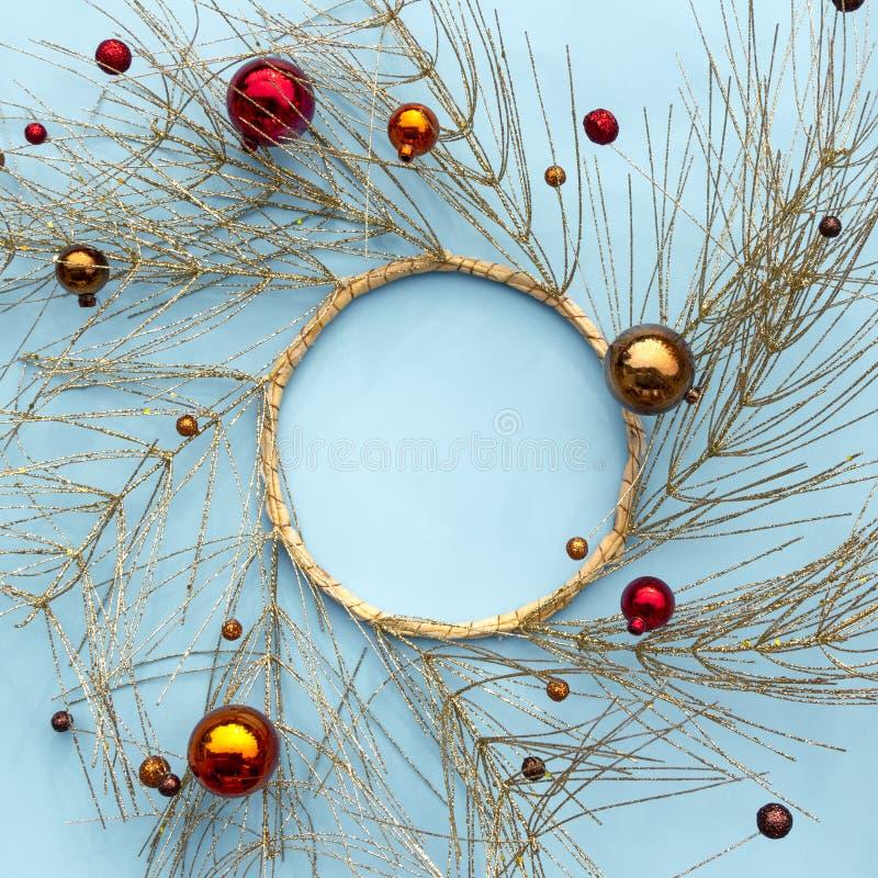Jul eller vintersammansättning för nytt år Rund ram som göras av guld- trädfilialer och röda dekorativa julprydnader på blått arkivbild
