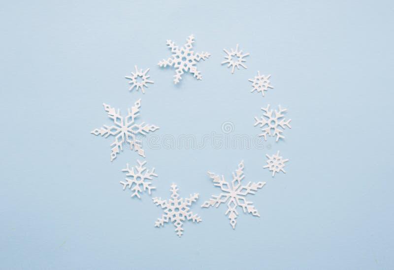 Jul eller vintersammansättningskrans Ram av vita snöflingor på pastellfärgad blå bakgrund Jul vinter, nytt ?r royaltyfria bilder