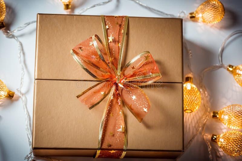 Jul en guld- gåvaask med en röd pilbåge och en härlig glödande girland mot snön arkivfoton