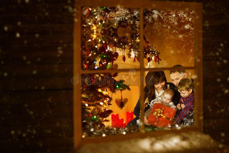 Jul fönster, familj som firar hemmet för Xmas-ferieinsida arkivbilder
