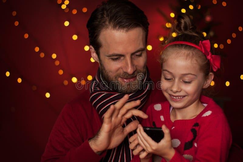 Jul - fader och dotter som spelar leken på mobiltelefonen royaltyfria bilder