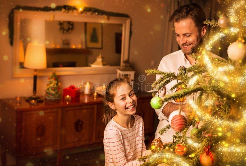 Jul - fadern och dottern dekorerar julträdet fotografering för bildbyråer