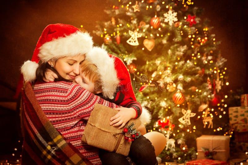Jul familj och Xmas-trädet, den lyckliga modern att ge sig behandla som ett barn barnet gåvagåvan för det nya året arkivfoto