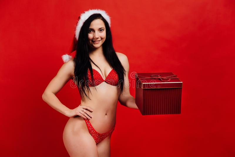 Jul ferier för ` s för nytt år Härlig flicka för sexiga sportar i bikinin Santa Claus med gåvaasken fotografering för bildbyråer