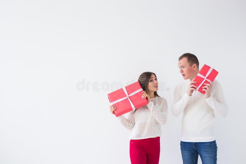 Jul, ferier, valentin dag och födelsedagbegrepp - den lyckliga mannen och kvinnan rymmer askar med gåvor på vit arkivbild