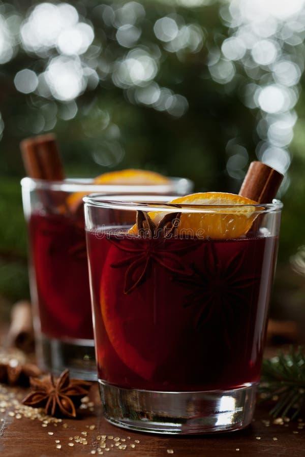 Jul funderade vin eller gluhwein med kryddor och apelsinskivor på den lantliga tabellen, traditionell drink på vinterferie, magis fotografering för bildbyråer