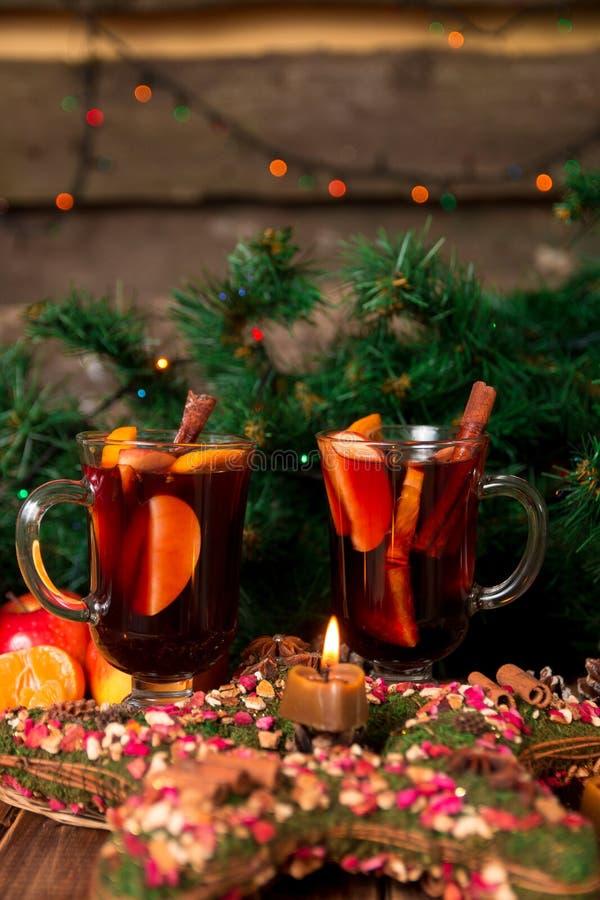 Jul funderade vin med frukter och kryddor på trätabellen Xmas-garneringar i bakgrund exponeringsglas två Vintervärmedrink r royaltyfri bild