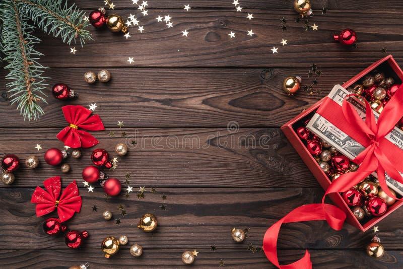 Jul gåva, pengar som packas med det röda spelrummet, Xmas-objekt, på en träbakgrund Top beskådar Utrymme för text arkivbild