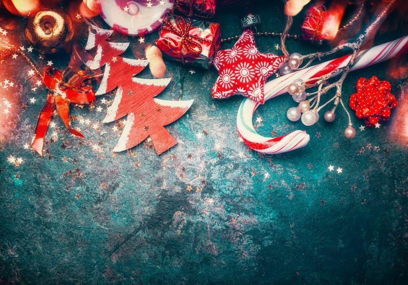 Jul gränsar med röd garnering, julträdet och godisen på mörker - blå tappningbakgrund royaltyfria bilder