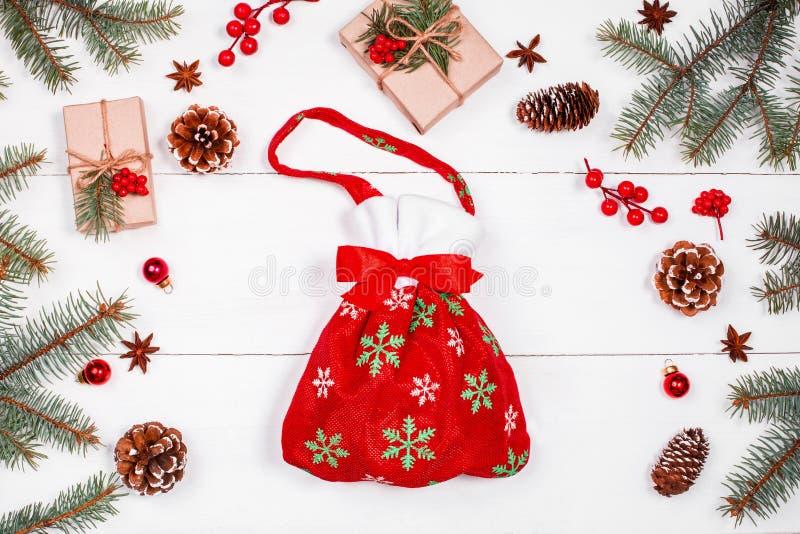 Jul hänger löst med gåvor på feriebakgrund med gåvor, granfilialer, sörjer kottar, röda garneringar Xmas och lyckligt nytt år arkivbild