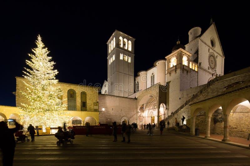 Jul 2017 i Assisi Umbria, med en sikt av San Francesco den påvliga kyrkan på natten, med det stort tänt trädet och folk arkivbild