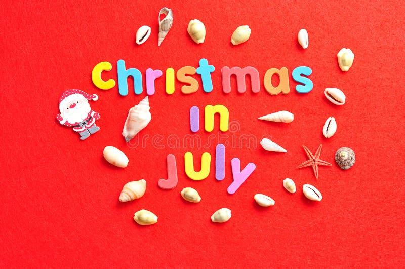 Jul i Juli med en samling av skal och ett Santa Claus diagram royaltyfri fotografi