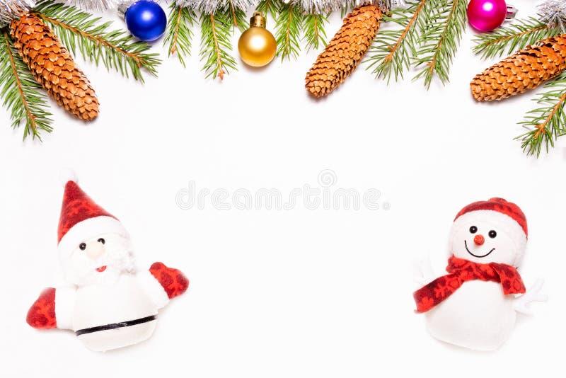 Jul inramar gjort av granfilialer som dekoreras med den isolerade Santa Claus och snögubben på vit bakgrund arkivbilder