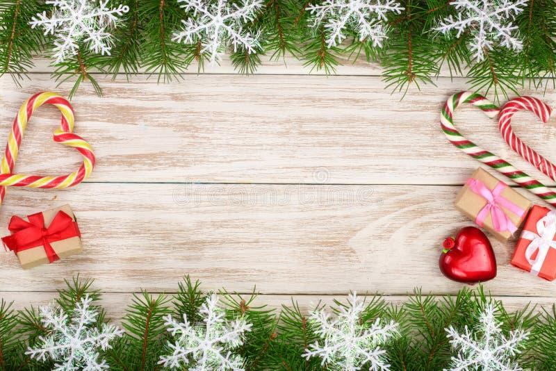 Jul inramar gjort av granfilialer som dekoreras med snöflingagodisrottingar och askar på en ljus träbakgrund arkivfoton