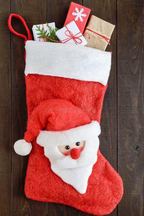 Jul kängan för ` s för det nya året för gåvor med jultomten vänder mot, fullt av gåvaaskar på en mörk träbakgrund royaltyfria bilder