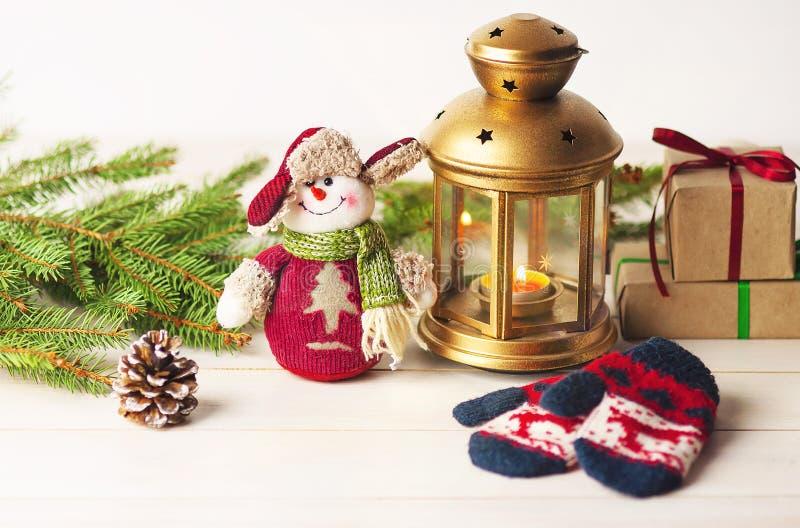 Jul klumpa ihop sig, garneringar på en träbakgrund med prydliga filialer, med en snögubbe och en ficklampa royaltyfri fotografi