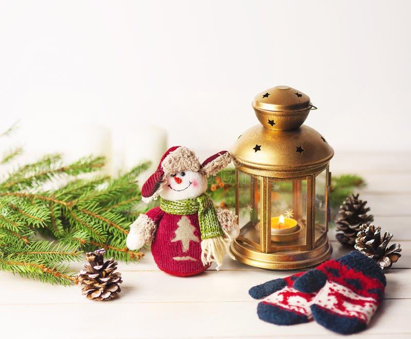 Jul klumpa ihop sig, garneringar på en träbakgrund med prydliga filialer, med en snögubbe och en ficklampa fotografering för bildbyråer