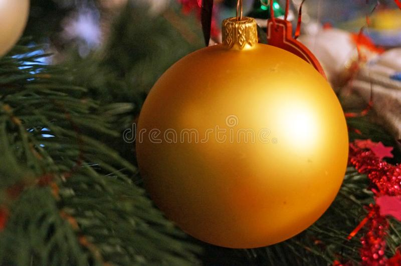 Jul klumpa ihop sig gul, röd, vit, blå, guld- blå hängning på en julgranfilial arkivfoto