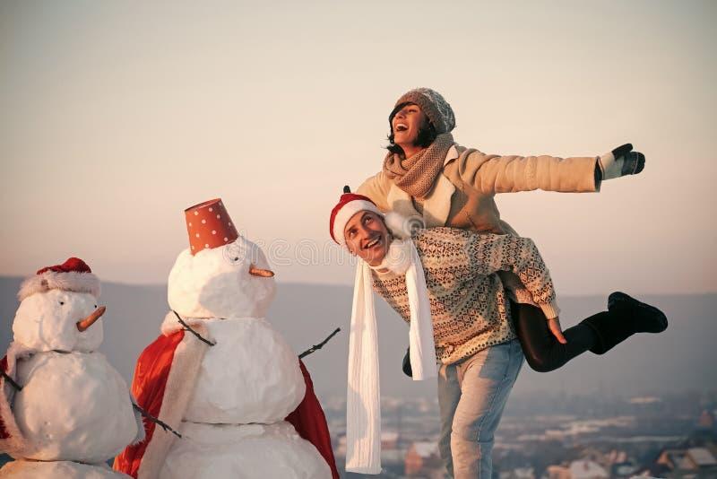 Jul kopplar ihop förälskat av mannen och flickan med snögubben arkivfoto