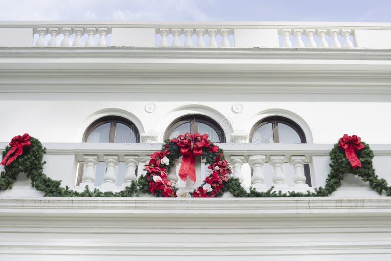 Jul krans och Garland Hanging från en vit herrgård arkivfoto