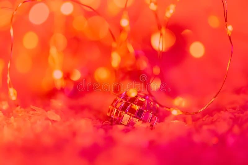 Jul Liten dekorativ boll med en spegel och en blänka girland på en snö Suddig festlig röd bakgrund med bokeh royaltyfri bild
