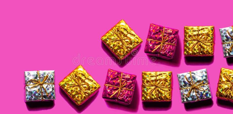 Jul mönstrar gjort av rött, guld med silvergåvaaskar som isoleras på rosa färgfärgbakgrund arkivfoton