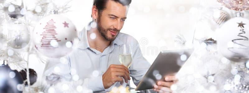 Jul man att se den digitala minnestavlan och drinkarna en glass nolla royaltyfri fotografi