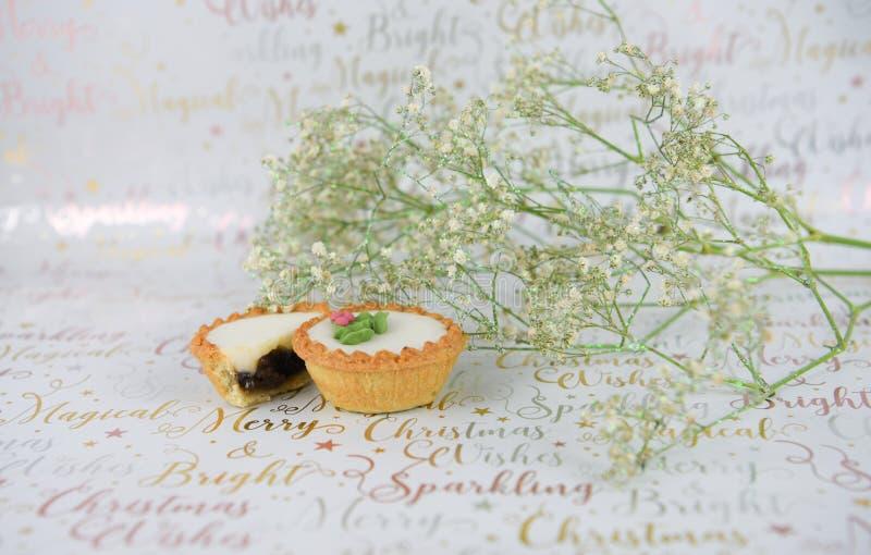 Jul mat somfotografi av vitgräsplan blommar med, blänker och färspajer på bakgrund för xmas-inpackningspapper fotografering för bildbyråer