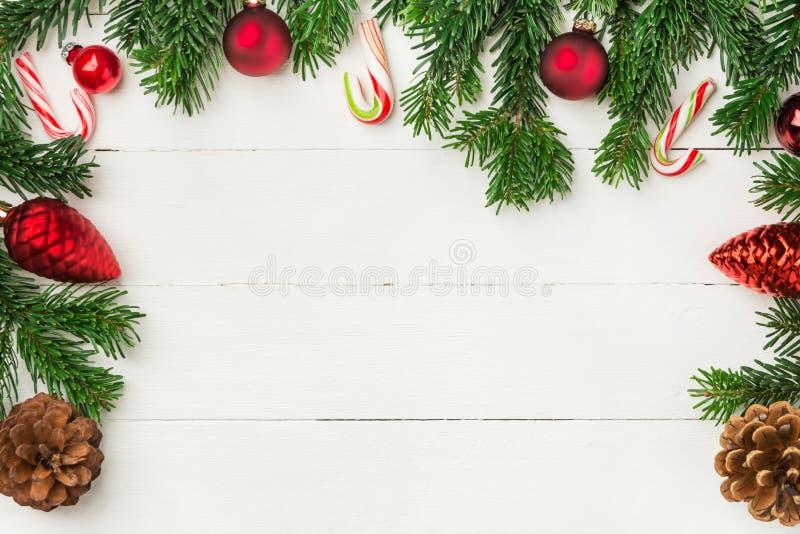 Jul, ny Ålderbakgrund i återgivningsstil med färska fluffy fir-grenar av rött prydnadsbollar och godis på trä royaltyfri fotografi