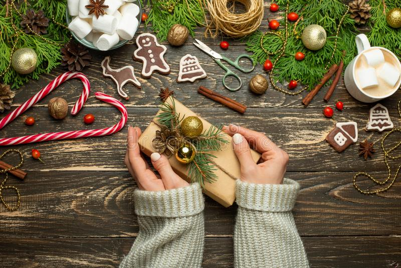 Jul nytt års bakgrund som lägenhet-är lekmanna- flickan i en woolen tröja slår in gåvor på en träbakgrund, med sörjer kottar, god arkivbild