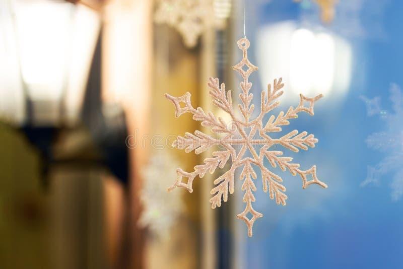 Jul och för prydnadgarnering för nytt år som snowlake räckas nära fönster med den lattern varma lampan på bakgrund Kort för vinte fotografering för bildbyråer