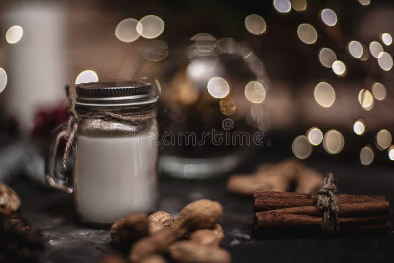 Jul och garneringbakgrund för nytt år med den runda bokehgirlanden, kanel, kakor, kottar, muttrar och stearinljuset i kopp royaltyfria bilder