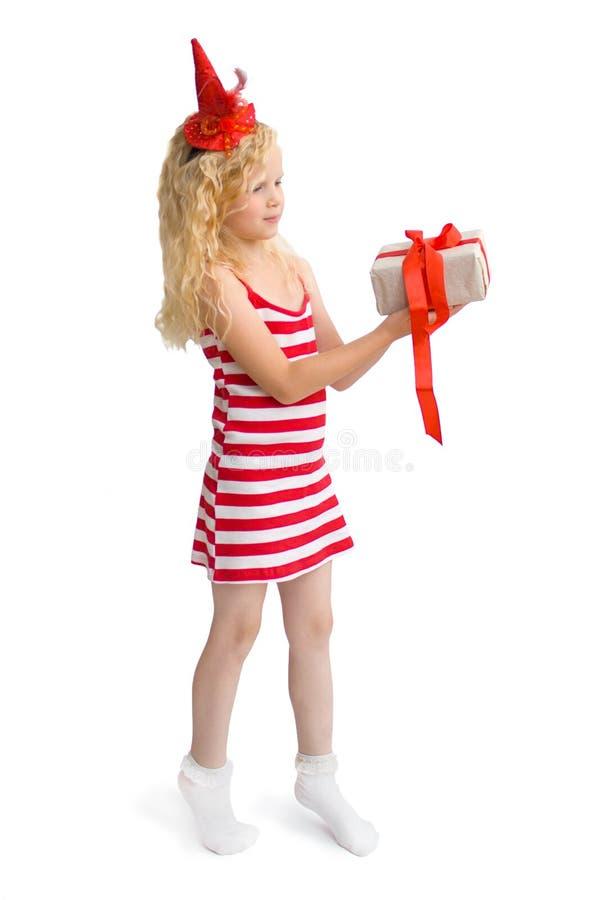 Jul och kort för nytt år med den lyckliga gulliga lilla blonda flickan i röd och vit karnevaldräktklänning med gåvaasken i händer royaltyfri bild