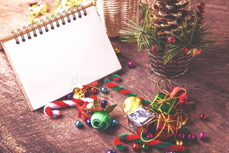 Jul och träbakgrundsbaner för nytt år med den tomma anteckningsboken, gåvaask, tusenskönablomma, royaltyfri bild