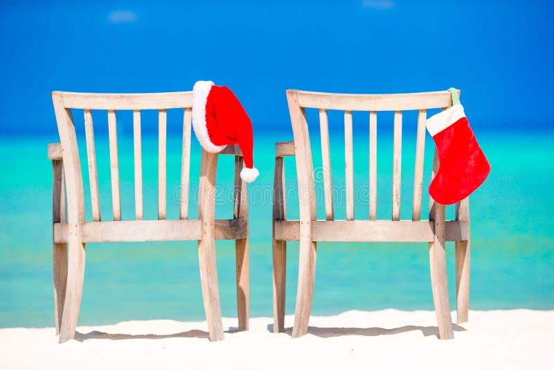 Jul på strandstolar i kafé med jultomtenhattar på havet royaltyfri fotografi