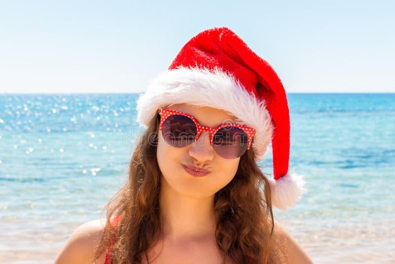 Jul sätter på land hatten för jultomten för kvinnan för semesterloppståenden som den bärande tycker om jul på den tropiska strand arkivbild