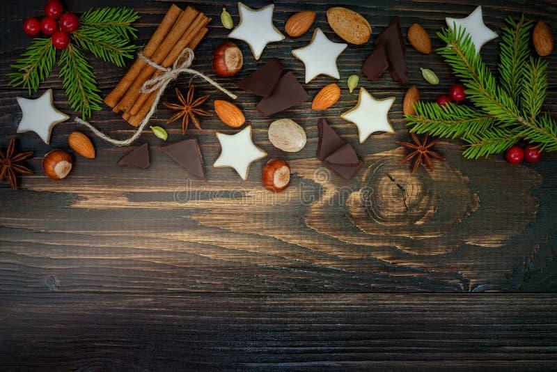 Jul semestrar bakgrund med pepparkakakakor, kryddor, och gran förgrena sig på det gamla träbrädet kopiera avstånd royaltyfri fotografi