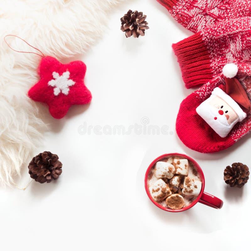 Jul semestrar varm choklad med marshmallowen, kotten, vit päls, den röda filtstjärnan, stack sockor på vit bakgrund arkivfoto